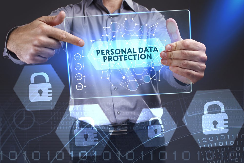 "man holding holographic tablet labeled ""personal data protection"" and lock icons against a backdrop of data"
