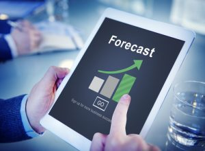 A supply chain executive holding tablet showing forecast
